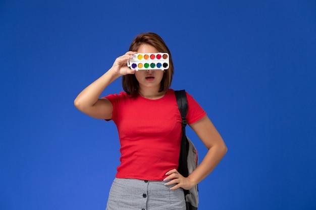 Vista frontal de la estudiante en camisa roja con mochila sosteniendo pinturas para dibujar en la pared azul