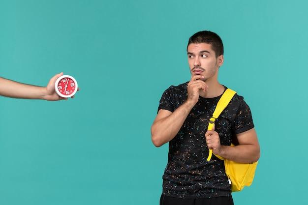 Vista frontal del estudiante en camiseta oscura mochila amarilla pensando en la pared azul claro