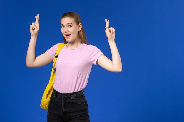 Vista frontal de la estudiante en camiseta rosa con mochila amarilla cruzando los dedos sobre la pared azul