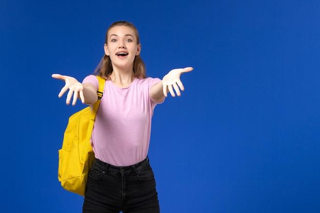Vista frontal de la estudiante en camiseta rosa con mochila amarilla en la pared azul claro