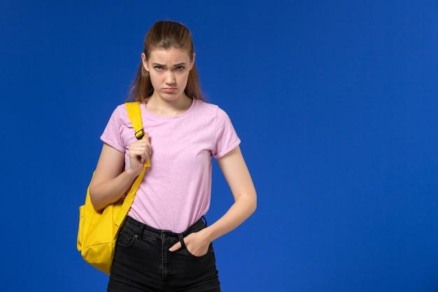 Vista frontal de la estudiante en camiseta rosa con mochila amarilla posando con expresión enojada en la pared azul