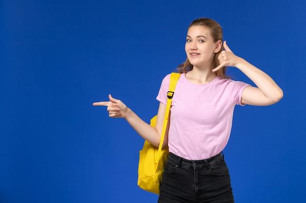 Vista frontal de la estudiante en camiseta rosa con mochila amarilla posando sonriendo en la pared azul claro