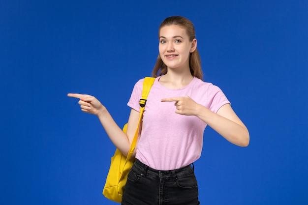 Vista frontal de la estudiante en camiseta rosa con mochila amarilla sonriendo en la pared azul