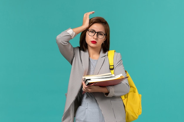 Vista frontal de la estudiante en chaqueta gris mochila amarilla sosteniendo libros en la pared azul claro