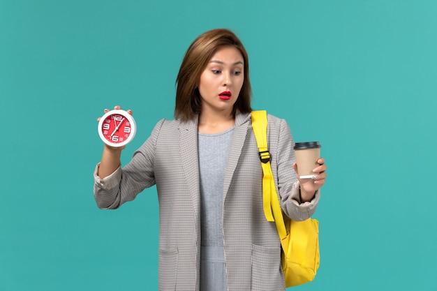 Vista frontal de la estudiante en chaqueta gris con su mochila amarilla sosteniendo relojes y café en la pared azul