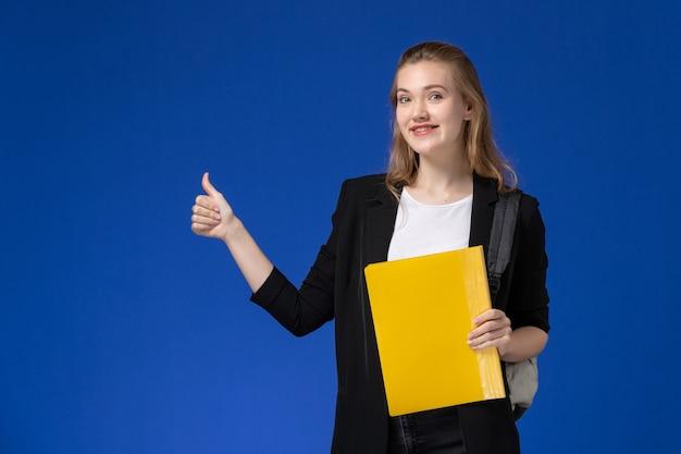 Vista frontal estudiante en chaqueta negra con mochila y sosteniendo un archivo amarillo en la lección de la universidad de la escuela de la pared azul