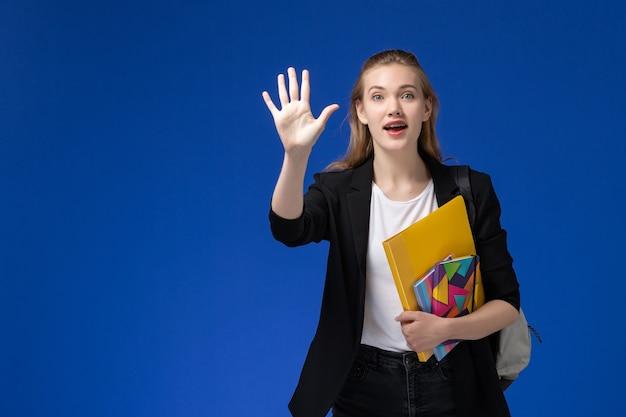 Vista frontal estudiante en chaqueta negra con mochila sosteniendo archivos con cuadernos en la lección de la universidad de la universidad de la pared azul claro