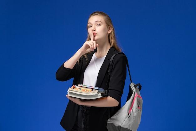 Vista frontal de la estudiante en chaqueta negra con mochila sosteniendo libros sobre el escritorio azul lección universitaria de la universidad de la escuela