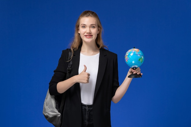 Vista frontal de la estudiante en chaqueta negra con mochila sosteniendo pequeño globo en la pared azul escuela colegio universidad tierra