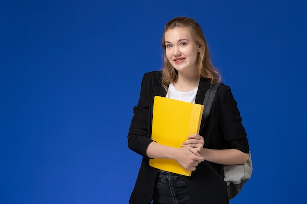 Vista frontal estudiante femenina en chaqueta negra con mochila y sosteniendo un archivo amarillo en la pared azul lecciones de la universidad de la escuela de la escuela
