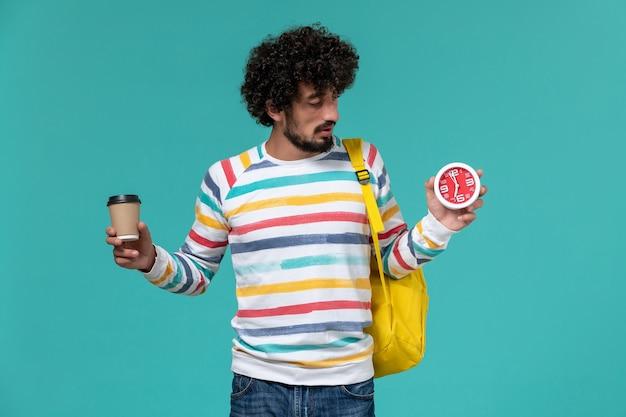 Vista frontal del estudiante masculino en camisa a rayas con mochila amarilla sosteniendo café y relojes en la pared azul