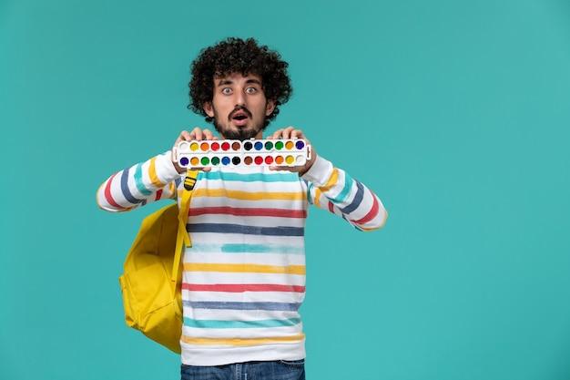 Vista frontal del estudiante masculino en camisa a rayas con mochila amarilla sosteniendo pinturas en la pared azul claro