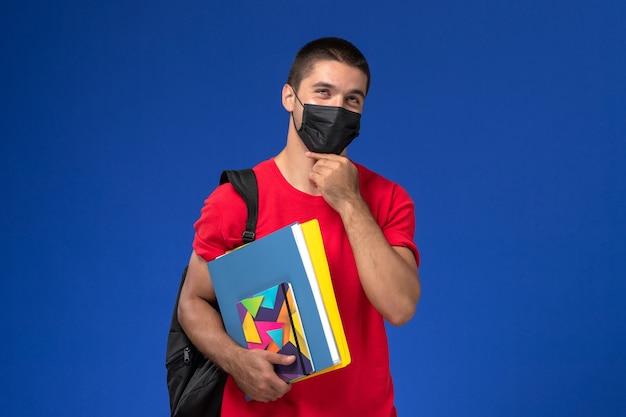 Vista frontal estudiante masculino en camiseta roja con mochila en máscara estéril negra sosteniendo cuadernos pensando en el fondo azul.