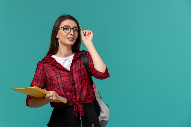 Vista frontal de la estudiante con mochila y sosteniendo archivos en la pared azul claro
