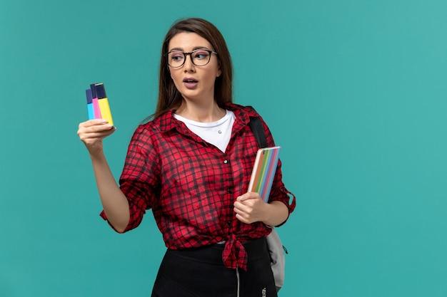 Vista frontal de la estudiante con mochila sosteniendo cuaderno y rotuladores en la pared azul