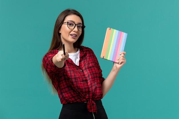 Vista frontal de la estudiante sosteniendo un cuaderno y un bolígrafo en la pared azul claro