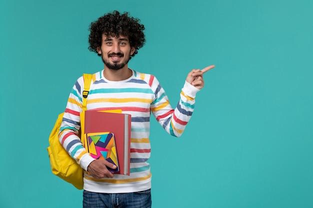 Vista frontal del estudiante varón con mochila amarilla sosteniendo archivos y cuaderno sobre pared azul