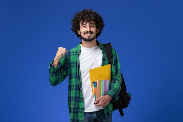 Vista frontal del estudiante varón con mochila negra sosteniendo cuadernos y archivos en la pared azul