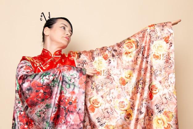 Una vista frontal exquisita geisha japonesa en vestido tradicional rojo japonés posando con tejido de flores elegante en la ceremonia de fondo crema japón
