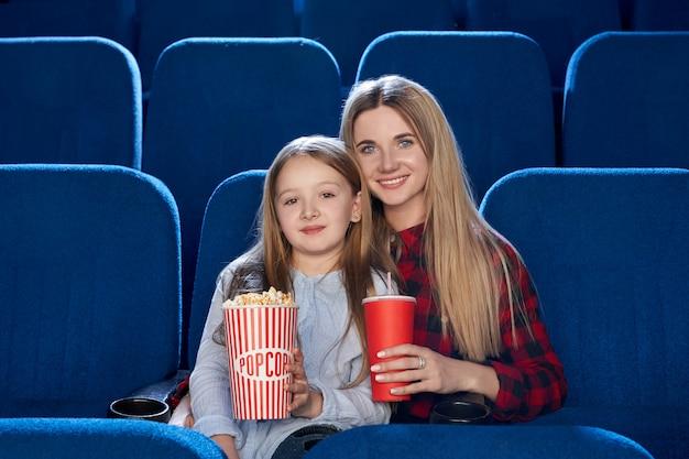 Vista frontal de la familia feliz pasar tiempo juntos en el cine.