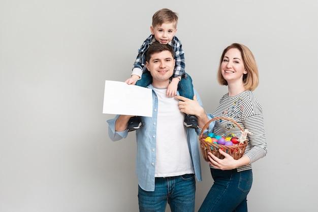 Vista frontal familia feliz posando con huevos de pascua