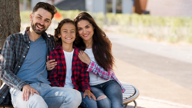 Vista frontal de la familia con el niño y los padres al aire libre con espacio de copia