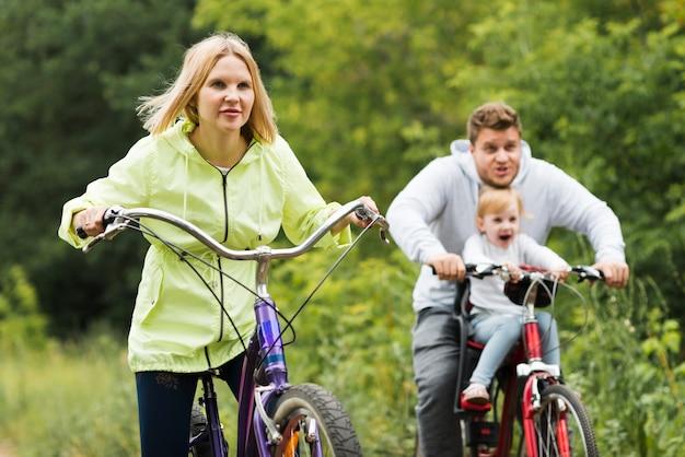 Vista frontal de la familia pasando un buen rato con las bicicletas.