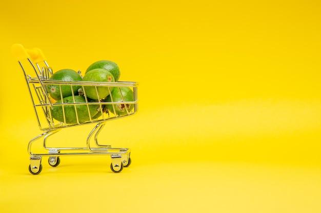 Vista frontal de la feijoa verde fresca dentro de la pequeña canasta móvil en la superficie amarilla de frutas exóticas suaves de color