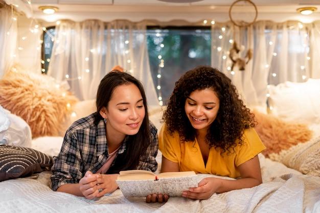 Vista frontal feliz amigas leyendo