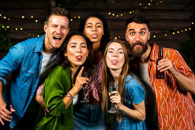 Vista frontal feliz amigos mostrando lenguas