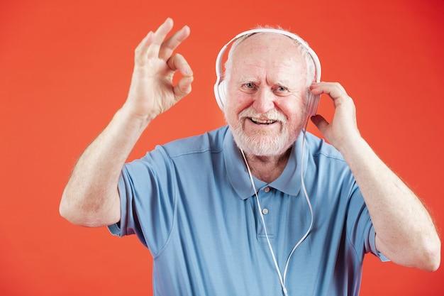 Vista frontal feliz anciano con auriculares