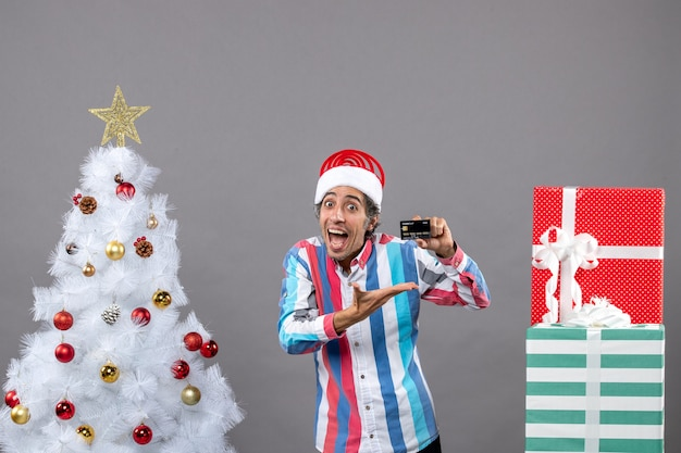 Vista frontal feliz joven mostrando su tarjeta de crédito cerca del árbol de navidad