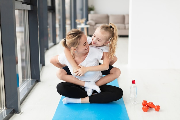 Vista frontal de la feliz madre y el niño en la estera de yoga con pesas