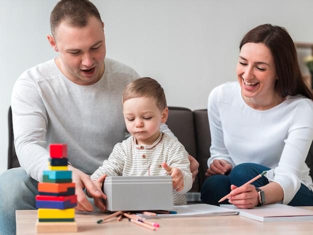 Vista frontal de la feliz madre y padre con niño en casa