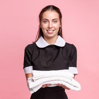 Vista frontal feliz mucama con toallas blancas