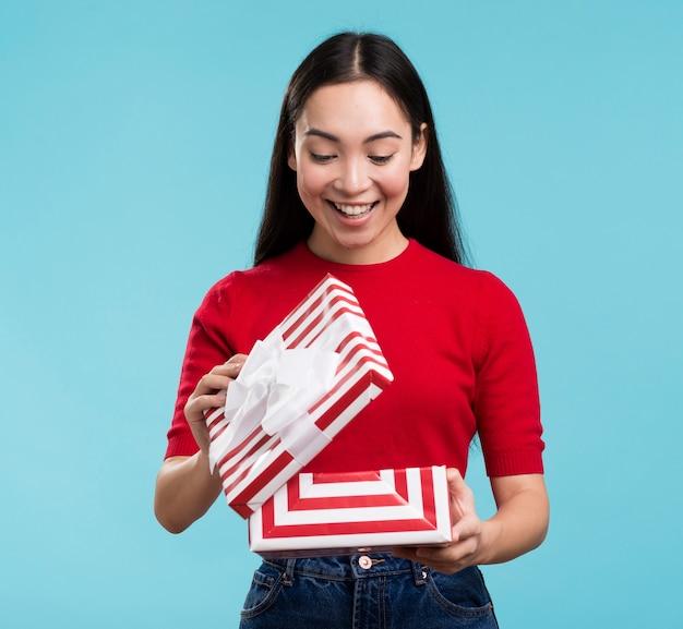 Vista frontal feliz mujer abriendo la caja de regalo