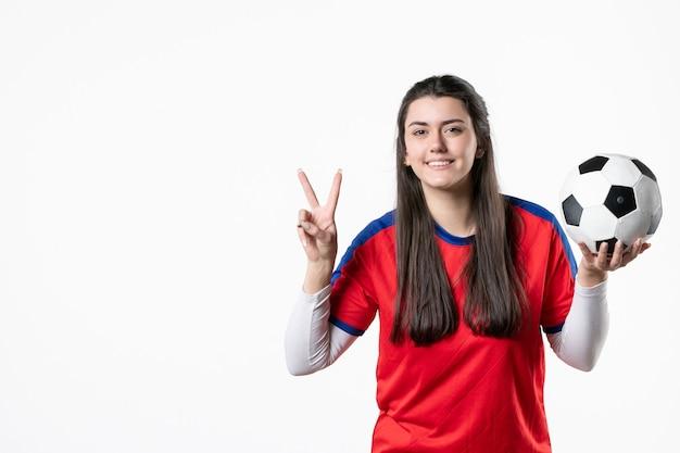 Vista frontal feliz mujer joven en ropa deportiva con balón de fútbol