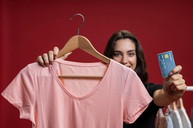 Vista frontal feliz mujer lista para comprar una camisa rosa
