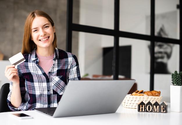 Vista frontal feliz mujer con tarjeta de crédito