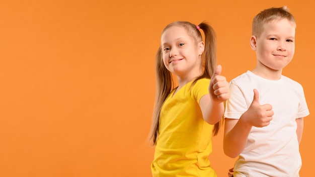 Vista frontal feliz niño y niña mostrando los pulgares para arriba