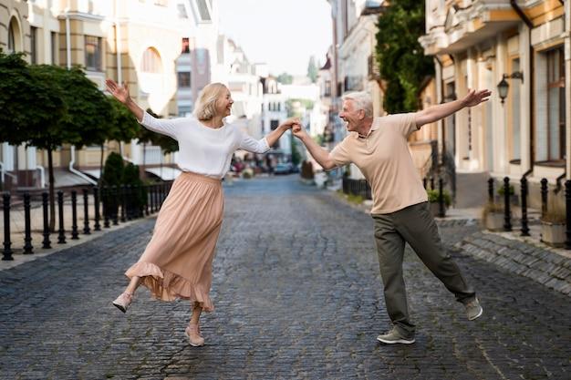 Vista frontal de la feliz pareja de ancianos en la ciudad