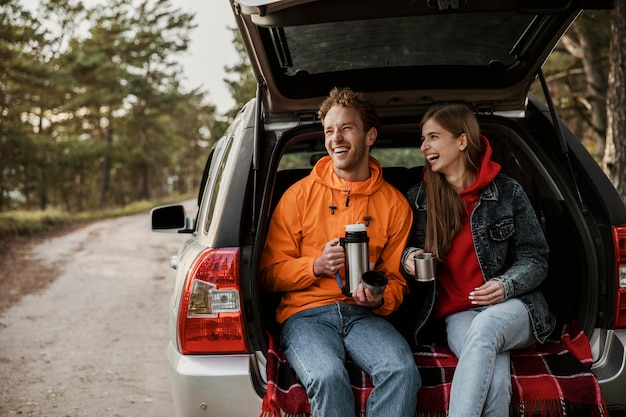 Vista frontal de la feliz pareja disfrutando de una bebida caliente en el maletero del coche