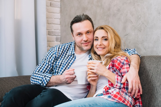 Vista frontal de la feliz pareja joven sosteniendo la taza de café sentado en el sofá