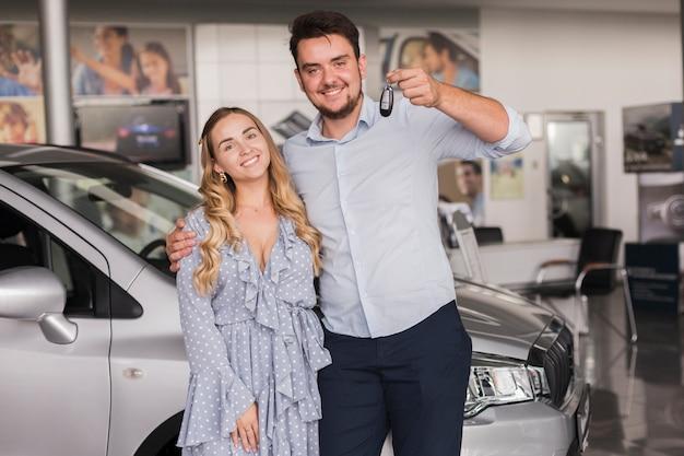 Vista frontal feliz pareja sosteniendo las llaves del auto