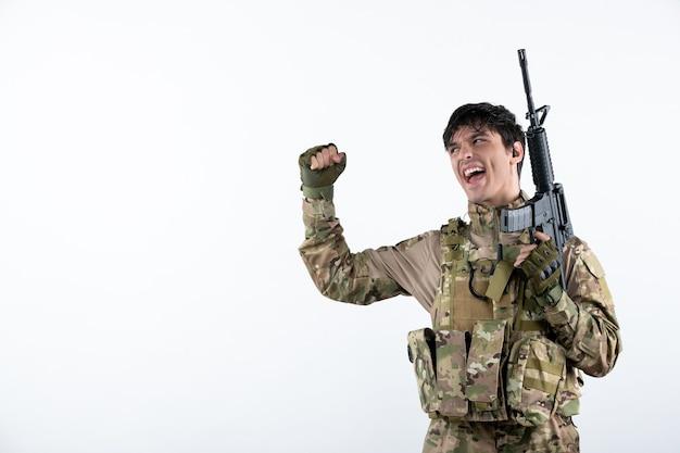 Vista frontal del feliz soldado masculino con ametralladora en camuflaje en la pared blanca