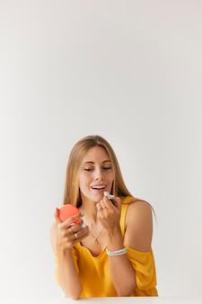 Vista frontal femenina tratando de brillo labial