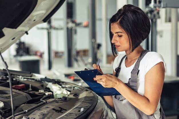 Vista frontal femenino mecánico inspeccionando coche