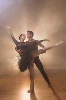 Vista frontal figurante sosteniendo bailarina