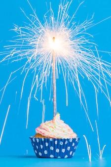 Vista frontal fila cupcake cumpleaños con bengala