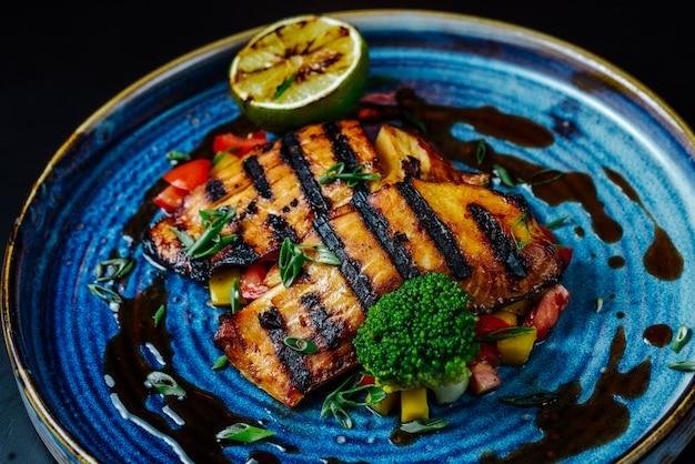 Vista frontal filete de pescado a la parrilla con verduras y una rodaja de limón en un plato